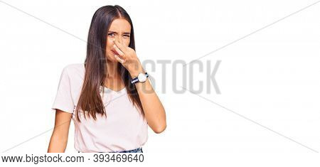 Young hispanic woman wearing casual white tshirt smelling something stinky and disgusting, intolerable smell, holding breath with fingers on nose. bad smell