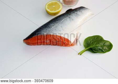 Fatty Salmon Carcass, Spinach And Lemon On A White Background.
