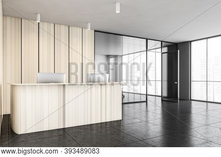Wooden Office Reception With Two Laptops And Separate Conference Room With Chairs For Client Service