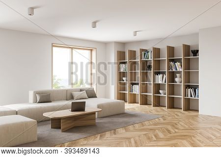 Interior Of Modern Living Room With White Walls, Wooden Floor, White Sofa And Coffee Table With Lapt