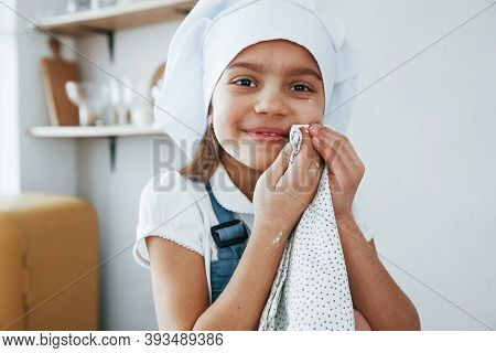 Cute Little Girl In Blue Chef Uniform Cleaning Her Face From Flour On The Kitchen.