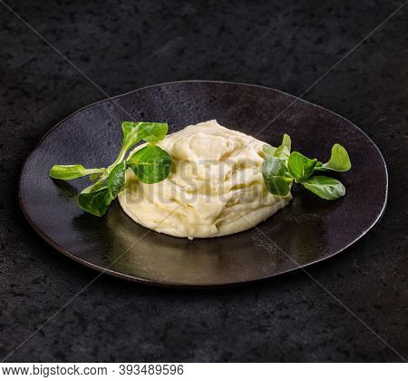 Portion Of Mashed Potatoes In Black Plate, Dark Background.