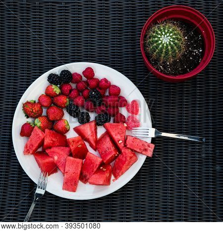 A White Plate With Slices Of Red Watermelon And Berries, Two Forks And A Red Flower Pot With A Cactu