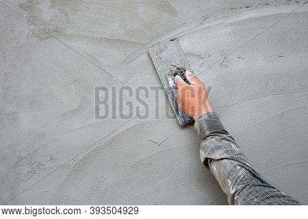 Plasterer Hand's Man Using Wooden Trowel To Plastering Concrete Wall In Construction Site