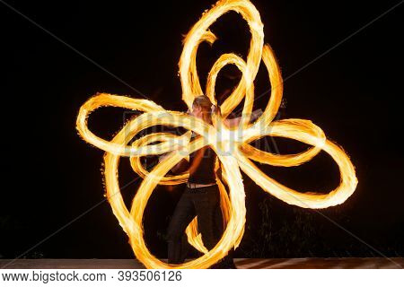 Expressive Style Couple Of Fire Dancers Spin Burning Pois Creating Sparkling Patterns On Dark Outdoo