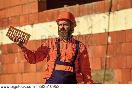 Brickwork. Man Takes Brick From The Pile. Male Construction Worker Holding Brick. Repairman Guy Hard