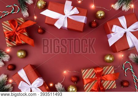 Red Background With Gifts, Decorations, Christmas Garland And Candy Cane. Place For Text. Xmas Flat
