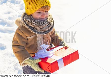 Kid In Winter Clothes Holds Christmas Gift. Kid During Stroll In A Snowy Winter Park. Beautiful Wint