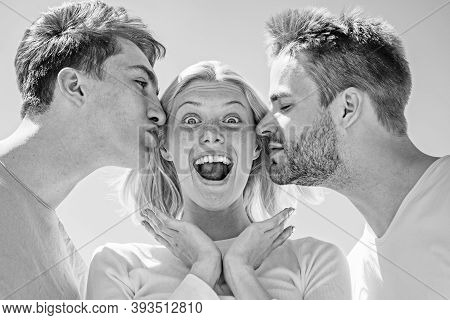 Blonde Happy Girl Getting Kisses From Two Handsome Boys. Charming Woman Standing Between Two Friends