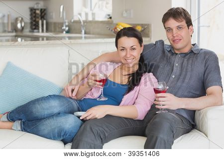 Young couple sitting on the couch in the living room while drinking wine