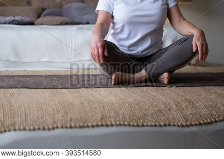 Woman Sitting On Mat Resting After Practice.