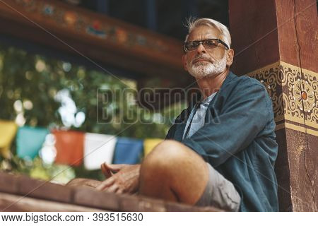 An Elderly European Tourist Meditates In An Asian Temple. A Pensioner Tourist Is Resting In An Old M
