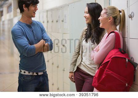 Friends talking in college hallway beside lockers
