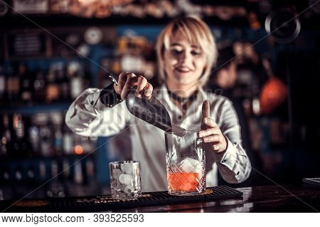 Pretty Woman Bartender Intensely Finishes His Creation While Standing Near The Bar Counter In Nightc