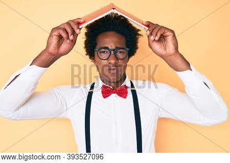 Handsome african american man with afro hair holding book over head skeptic and nervous, frowning upset because of problem. negative person.