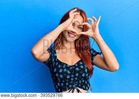 Young beautiful redhead woman wearing casual clothes over blue background doing heart shape with hand and fingers smiling looking through sign