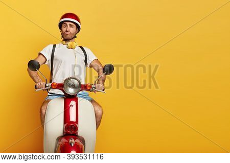 Funny Unshaven Caucasian Man Feels Proud To Have Own Fast Transport, Poses On Motorbike, Purses Lips
