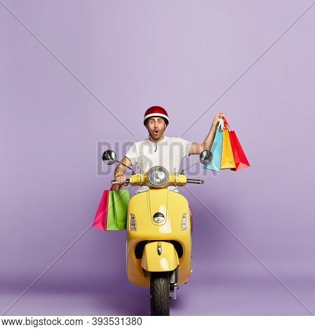 Vertical Image Of Impressed Handsome Guy In Casual Wear, Returns From Shop, Carries Shopping Bags, S