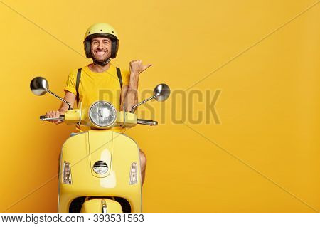People, Transport And Advertisement Concept. Cheerful Young European Male Motorcyclist Points Thumb