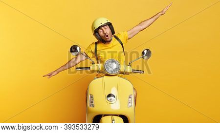 Impressed Young Male Motorcyclist Spreads Hands Sideways, Drives Motorbike, Enjoys Extreme Drive, We