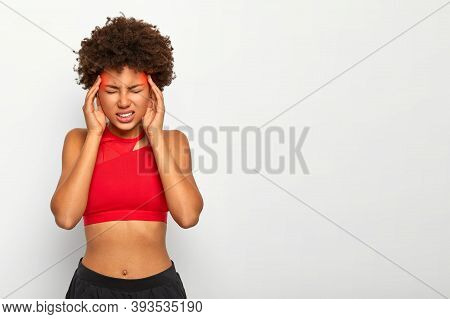 Horizontal Shot Of Dissatisfied African American Woman With Crisp Hair, Suffers From Terrible Pain I