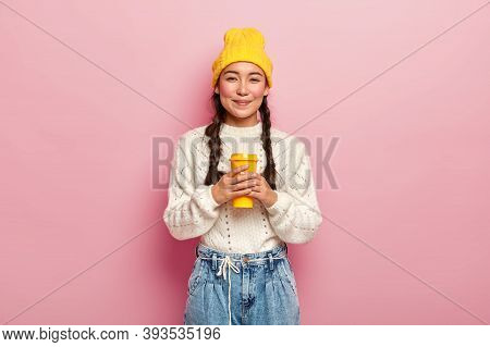 Pleased Attractive Woman With Plaits, Being Well Dressed, Enjoys Drinking Coffee From Takeout Cup, H