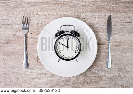 Knife And Fork With Alarm Clock On White Plate On Tablecloth Background. Intermittent Fasting, Ketog
