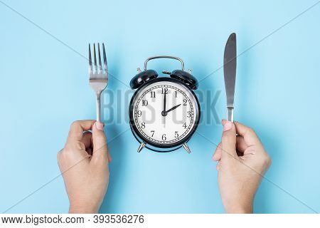 Hands Holding Knife And Fork Above Alarm Clock On White Plate On Blue Background. Intermittent Fasti
