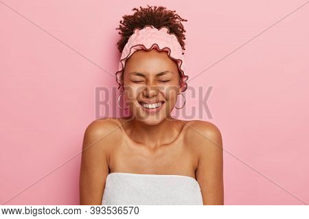 Photo Of Overjoyed Dark Skinned Woman Wrapped In White Bath Towel, Wears Pink Shower Headband, Preap