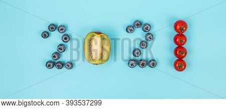 2021 Happy New Year And New You With Fruits And Vegetables; Blueberries, Kiwi And Tomato On Blue Bac