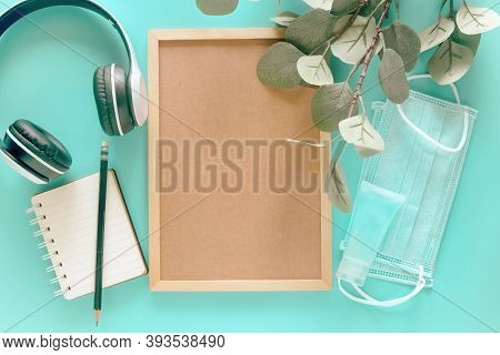 Blank Wooden Letter Board With Stationery Supplies, Medical Masks And Hand Sanitizer On Pastel Blue