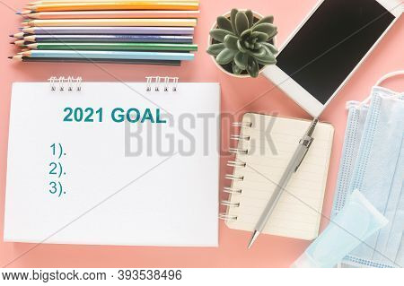 White Note With Word 2121 Goal With Stationary, Smartphone, Medical Masks And Hand Sanitizer On Past
