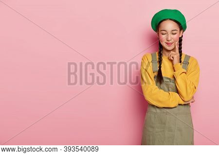 Pleasant Looking Satisfied Woman With Delighted Expression, Keeps Index Finger On Cheek, Eyes Shut,