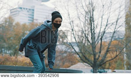 Young Blonde Woman With Face Mask Skating In The Skatepark In Autumn. High Quality Photo