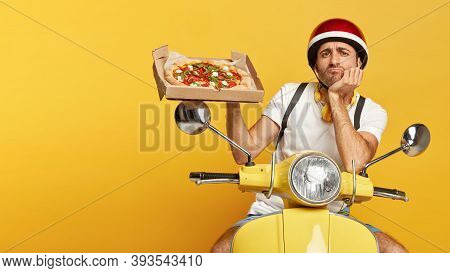 Photo Of Serious Dissatisfied Busy Pizza Man Shows Tasty Junk Food On Cardboard Box, Poses On Fast T