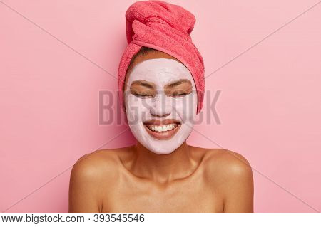 Headshot Of Pleasant Looking Dark Skinned Woman Applies Mud Mask On Face, Stands Bare Shoulders, Has