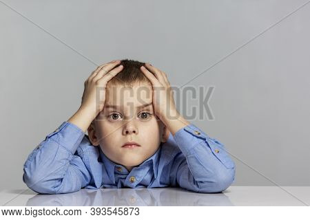 Sad Schoolboy Boy Sits At The Table And Holds His Head. Learning Difficulties. Gray Background. Spac