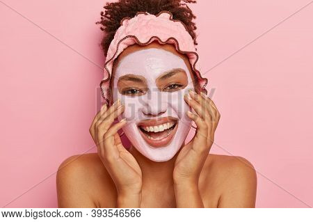 Facial Treatment Concept. Beautiful Cheerful Woman Poses With Clay Facial Mask, Smiles Broadly, Show