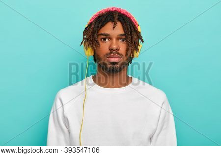 Portrait Of Handsome Confident Male With Dreadlocks, Wears Headphones Connected To Some Device, List