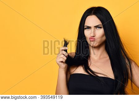 Frustrated Beautiful Brunette Woman Examining Looking At Her Dry Damaged Hair Over Yellow Background