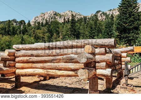 Framework. Wooden House Made Of Logs At The Initial Stage Of Construction. In The Background, The Fo