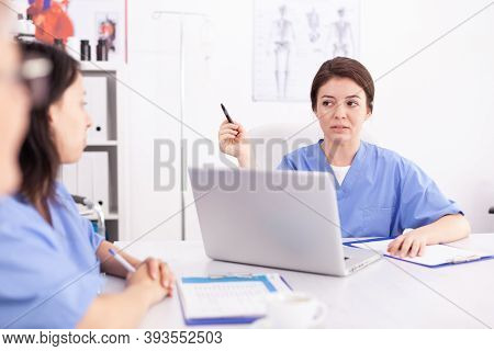 Medical Nurse Using Laptop During Briefing With Medicine Experts In Hospital Conference Room. Clinic