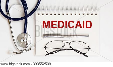Stethoscope,glasses And Pen With Notepad With Text A Medicaid On White Background