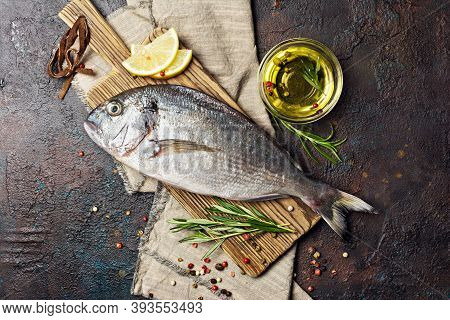 Fresh Fish Dorada Or Gilt-head Bream On Cutting Board With Spices, Olive Oil And Lemon