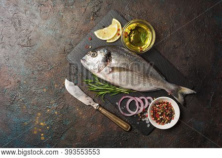 Fresh Fish Dorada Or Gilt-head Bream On Slate Board With Spices, Olive Oil And Lemon