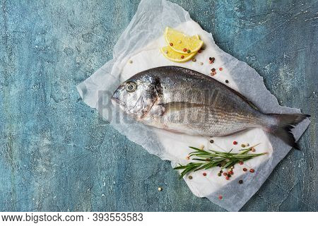 Fresh Fish Dorada Or Gilt-head Bream On Cutting Board With Spices And Lemon