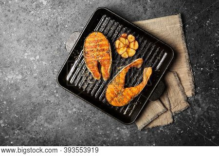 Spicy Fried Red Fish Salmon Steak On Grill Pan With Garlic