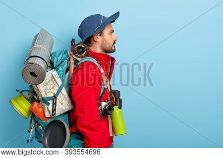 Profile Shot Of Serious Male Backpacker Stands With Big Rucksack, Carries Many Necessary Things For