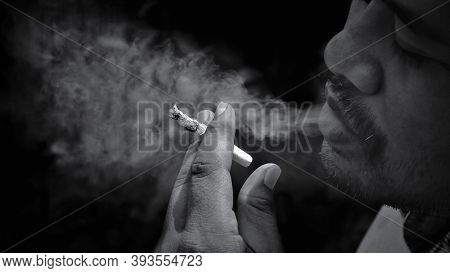 Focus At Hand And Close Up Man With Mustache Smoking Cigarette And Exhaling Smoke In Black And White
