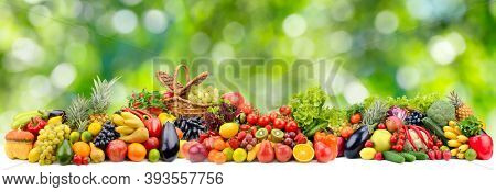 Panoramic collection bright fresh fruits and vegetables on blurred green background.